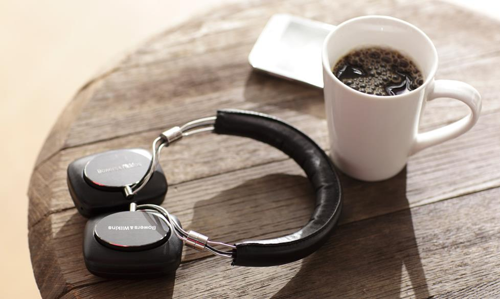 Headphones next to a coffee cup