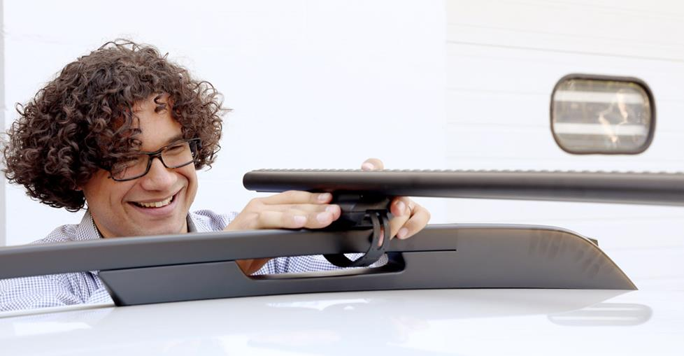 Mark secures the AeroBlade bars to the Subaru's roof rack.