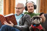Couple watching TV wearing wireless headphones