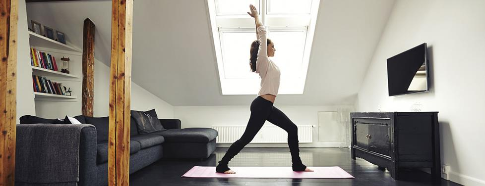 Woman doing yoga in her living room.