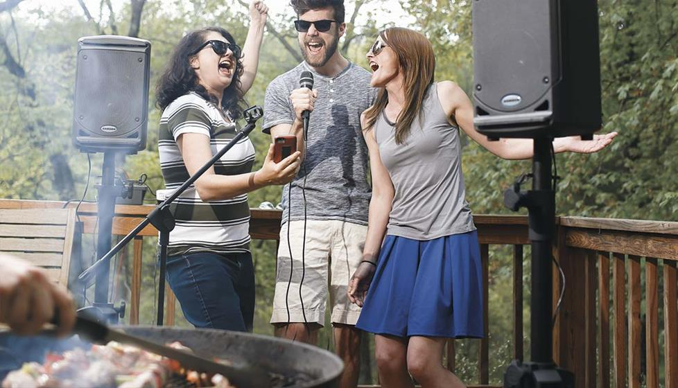 people singing outide on a deck with the Singtrix® Home karaoke system
