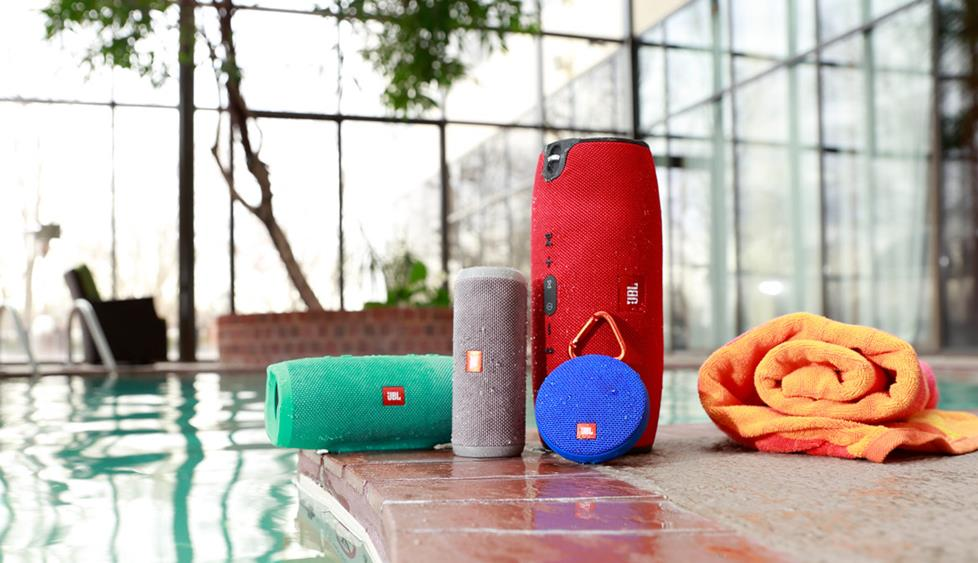Several bluetooth speakers, in assorted shapes and colors, beside a swimming pool.