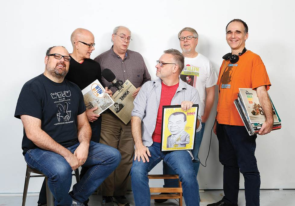 six guys posing with records and broadcast gear