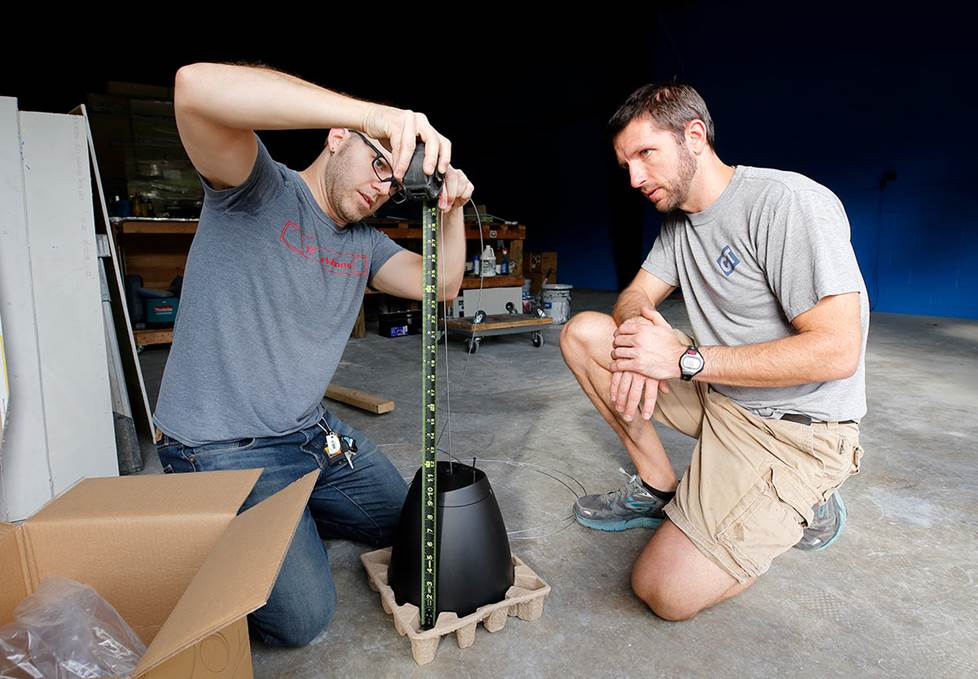two men measuring a speaker