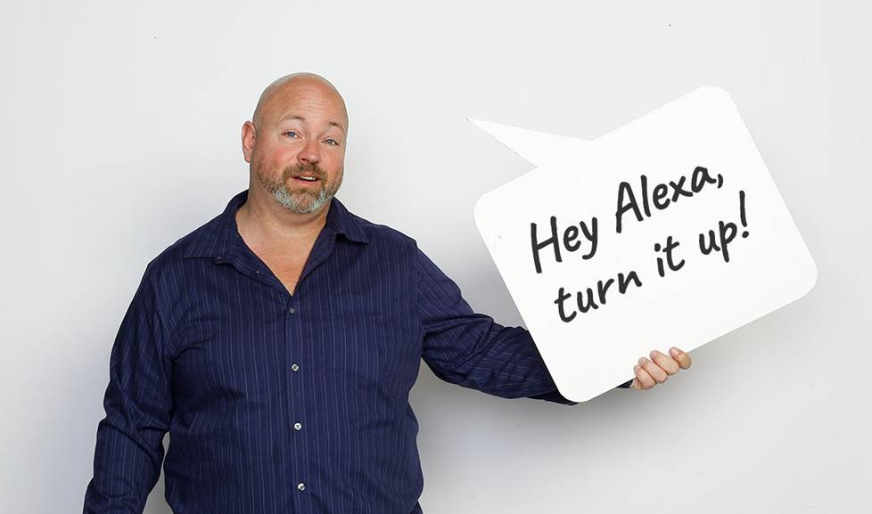 "man holds speech bubble that says ""Hey Alexa, turn it up!"""