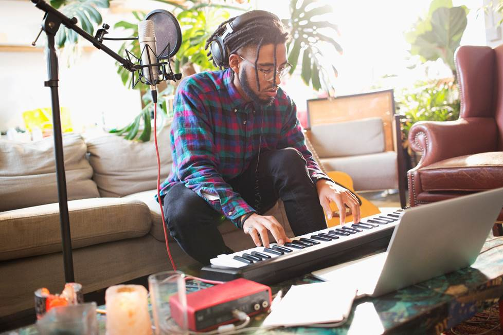 man recording music in his apartment