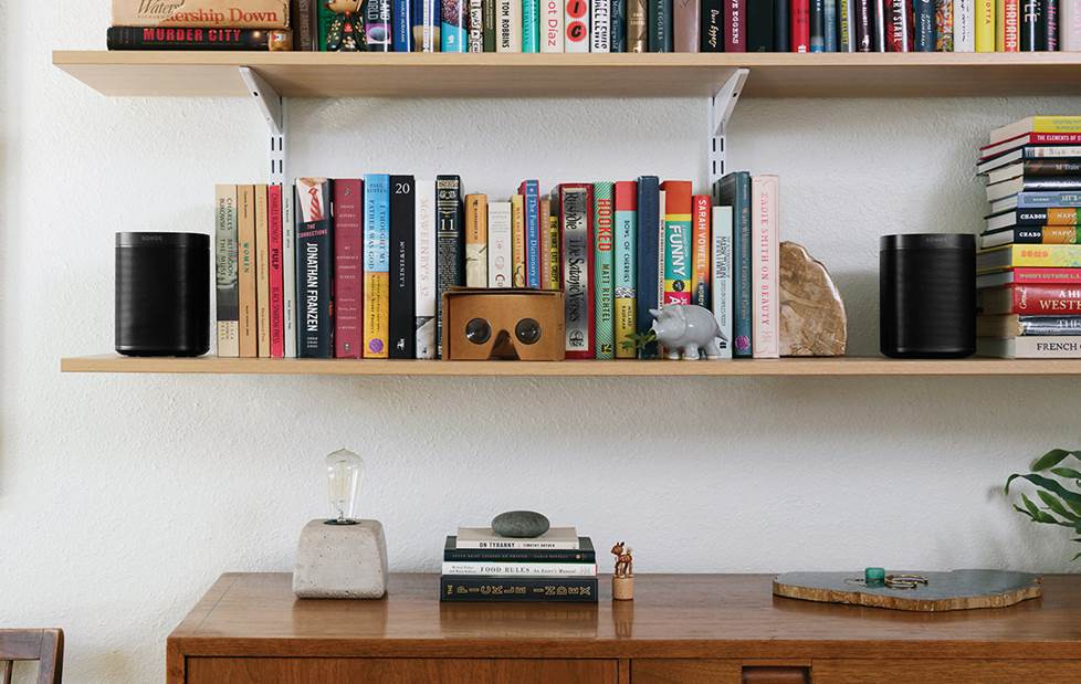 Two Sonos speakers on a bookshelf