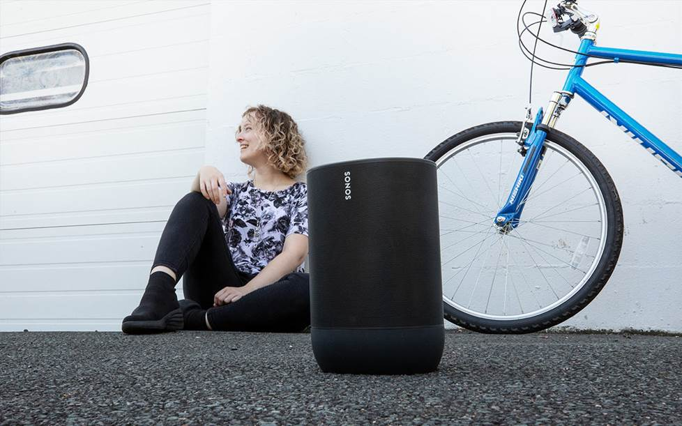 Woman outside with Sonos Move and bicycle